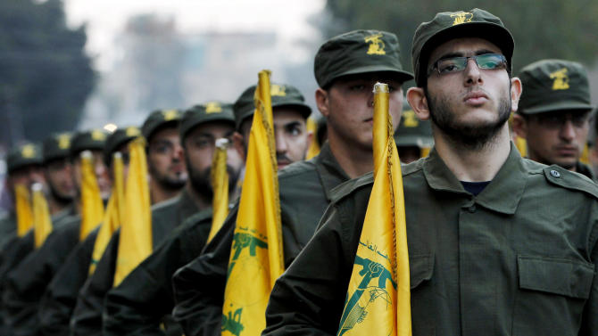 FILE - In this November 12, 2010 file photo, Hezbollah fighters hold their party flags, as they parade during the opening of new cemetery for colleagues who died in fighting against Israel, in a southern suburb of Beirut, Lebanon. Lebanon's prime minister has expressed his readiness to cooperate with Bulgarian authorities over a bomb attack linked to Hezbollah that killed five Israelis and their Bulgarian driver, in a statement Tuesday, Feb. 5, 2013. Prime Minister Najib Mikati whose Cabinet is dominated by members of the Shiite Muslim group and its allies also says he condemns and rejects any attack that targets an Arab or foreign country.(AP Photo/Hussein Malla, File)