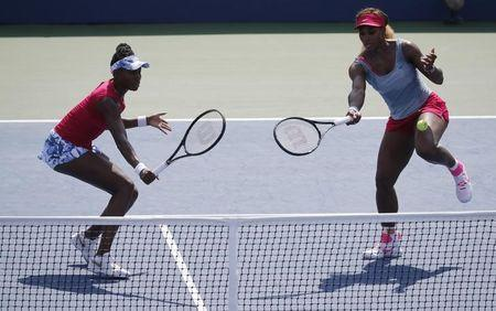 A ball hits Serena Williams as her sister Venus looks on as they play Makarova and Vesnina of Russia in their quarter-final doubles match at the 2014 U.S. Open tennis tournament in New York