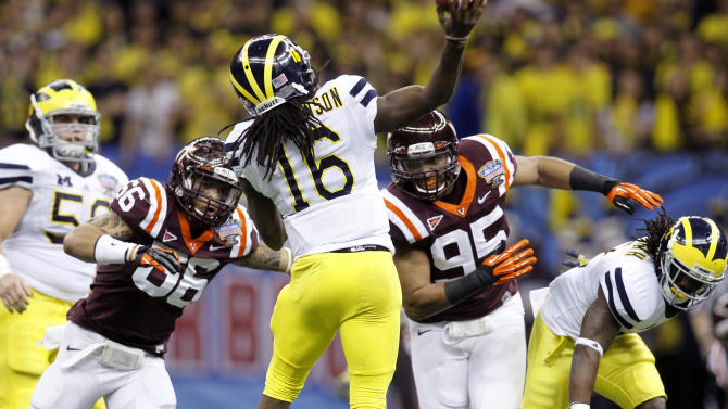 Michigan quarterback Denard Robinson (16) throws a touchdown pass under pressure from Virginia Tech defensive ends Tyrel Wilson (66) and Zach McCray (95) during the second quarter of the Sugar Bowl NCAA college football game in New Orleans, Tuesday, Jan. 3, 2012. (AP Photo/Bill Haber)