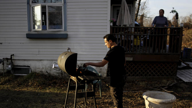 In this Monday, Dec. 3, 2012 photo, Rachael Alhadad looks on, as her husband, Amin Alhadad, lights a fire in the grill to cook their dinner at their home in the Midland Beach section of Staten Island, New York. In late November, FEMA finally put the Alhadads up in two rooms at a nearby Holiday Inn, where they'll stay until the federal money runs out on Dec. 15. After that, if their home is still uninhabitable, the family might be eligible for a two-month rental assistance grant from FEMA. But they haven't made plans and aren't sure what's next. (AP Photo/Seth Wenig)