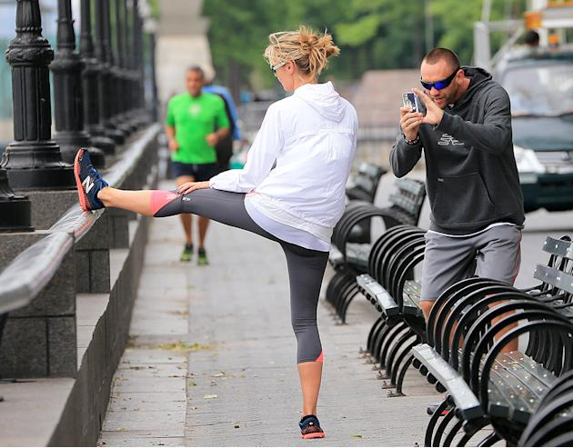Heidi Klum stretches while Martin Kristen takes a photo at a park in NYC