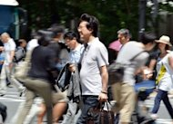 People cross a road in Tokyo in July 2012. Japan must do more to shrink its massive public debt, the International Monetary Fund said Wednesday, but added that the nation&#39;s disaster-hit economy was recovering well despite turmoil overseas