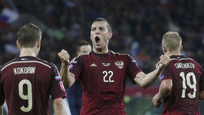 Russia's Dzyuba celebrates with team mates Kokorin and Smolnikov after scoring against Belarus during their Euro 2016 group G qualification match at Otkrytie Arena stadium in Moscow