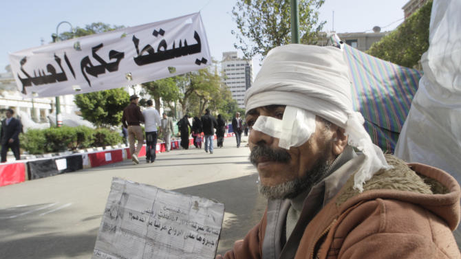 """Mohammed Hennaway, who was injured during recent clashes with security forces, sits in front of his tent during a protest demanding the ruling military council to step down in front of the cabinet office in Cairo, Egypt, Sunday, Dec. 4, 2011. The banner, in Arabic, reads """"down with military rule."""" (AP Photo/Amr Nabil)"""