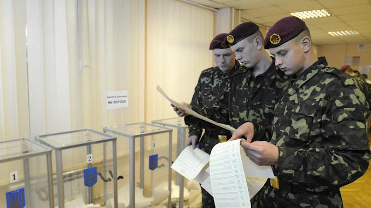 Ukrainian military examine their voting ballots at a polling station in  Kiev during  parliamentary elections in Ukraine Ukraine, Sunday, Oct. 28, 2012.(AP Photo/Sergei Chuzavkov)