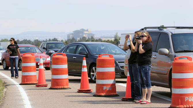 Motorists stop to take photographs along the southbound lanes of Interstate 25 as a wildfire rolls through housing subdivisions in the mountains north and west of Colorado Springs, Colo., on Wednesday, June 27, 2012. The fire has forced the evacuation of more than 32,000 residents of the communities west of, and now in Colorado Springs proper. (AP Photo/David Zalubowski)