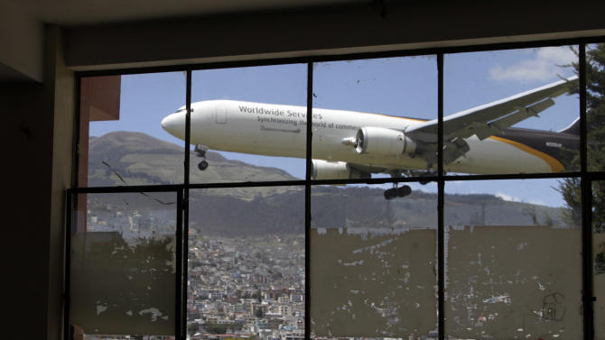 In this Jan. 8, 2013 photo, a plane approaches the Mariscal Sucre airport for landing, seen through a glass wall inside the Eloy Alfaro school in Quito, Ecuador.  Landing at Ecuador's capital can be a white-knuckle affair. High altitude, a cramped runway and towering, active volcanos nearby make it one of Latin America's most challenging aiports for pilots. And the constant roar of the planes has tormented those on the ground as well. Mariscal Sucre airport sat amid cornfields when it was christened in 1960, and on Feb. 19, the airport will close and a new airport will be built in an agricultural setting 12 miles (20 kilometers) northeast of the capital. (AP Photo/Dolores Ochoa)
