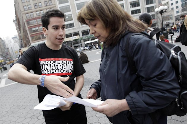 "In this Friday, March 16, 2012 photo, New York resident Cesar Andrade talks to a passerby about a petition to urge Gov. Andrew Cuomo to pass the Dream Act during a ""Coming Out of the Shadows"" rally in"