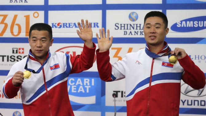 North Korea's Om Yun Chol and Kim Un Guk pose with their gold medals during a news conference at the 17th Asian Games in Incheon