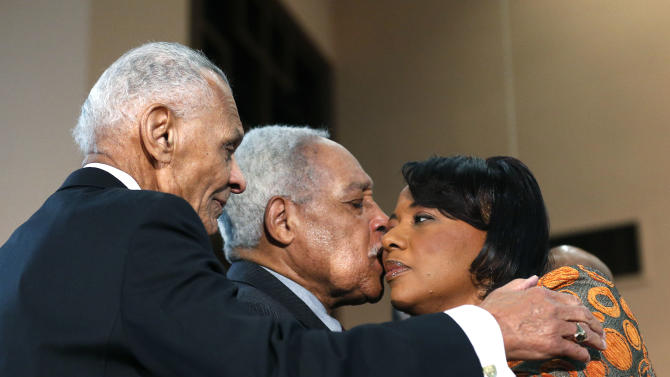 Bernice King, right, gets a kiss from Albert Brinson as Rev. C.T. Vivian looks on at left during a news conference Thursday, Feb. 6, 2014, in Atlanta, at the Ebenezer Baptist Church where her father Martin Luther King Jr. preached. King is in a legal battle with her brothers over her father's Bible and Nobel Peace Prize medal. (AP Photo/John Bazemore)