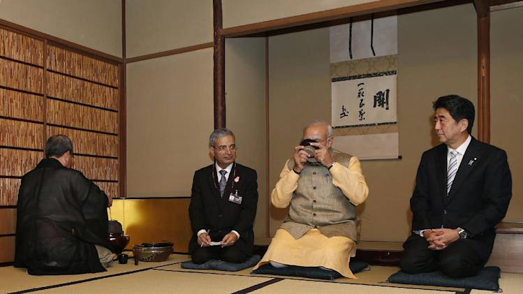 India's Prime Minister Narendra Modi, second right, drinks a bowl of rea as Japanese Prime Minister Shinzo Abe, right, looks on during a tea ceremony at a tea hut of the Omotesenke, one of the main schools of Japanese tea ceremony, in Tokyo Monday, Sept. 1, 2014. Modi was on his official visit to Japan. (AP Photo/Yuya Shino, Pool)