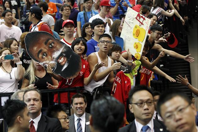 Holding a giant portrait of NBA Houston Rockets star James Harden, fans hope to meet the Rockets players after beating the Indiana Pacers during a preseason game in Taipei, Taiwan, Sunday, Oct. 13, 20
