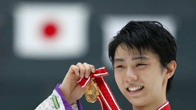 Gold medal winner in the men's single competition Hanyu Yuzuru of Japan show off his medal during the presentation ceremony at the ISU Grand Prix of Figure Skating in Nagano, Japan