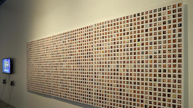 """This Tuesday, March 5, 2013, photo,  shows hundreds of images of people's faces taken from Facebook as part of Paolo CirioI's and Alessandro Ludovicoa's mixed media installation in """"The Public Private"""" exhibit at the Anna-Maria and Stephen Kellen Gallery in the Sheila C. Johnson Design Center at Parsons The New School for Design in New York.  The exhibit seeks to explore the boundaries and gray areas of online privacy, surveillance and data collection in the age of Facebook and Google. (AP Photo/Kathy Willens)"""