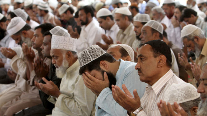 """Pakistani worshippers pray for the recovery of 14-year-old schoolgirl Malala Yousufzai, who was shot on Tuesday by the Taliban for speaking out in support of education for women, during Friday prayers in a Mosque in Karachi, Pakistan, Friday, Oct. 12, 2012. A Pakistani military spokesman says Yousufzai is in """"satisfactory"""" condition but cautions that the next few days will be critical. (AP Photo/Fareed Khan)"""