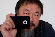 Artist Ai Weiwei holds a webcam that he was reportedly ordered by Chinese police to disconnect, at his home in Beijing on April 5. Dissident artist Ai Weiwei warned the Chinese government that its attempts to censor the internet would inevitably fail, in an article published in Monday's Guardian newspaper