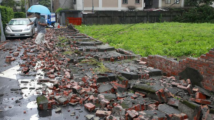 A man walks over fallen bricks from a wall that was blown over by strong winds from Typhoon Matmo which hit Taiwan, in Taipei