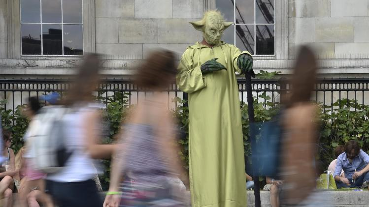 "A street entertainer dressed as ""Yoda"" from Star Wars performs an optical illusion in Trafalgar Square in London"