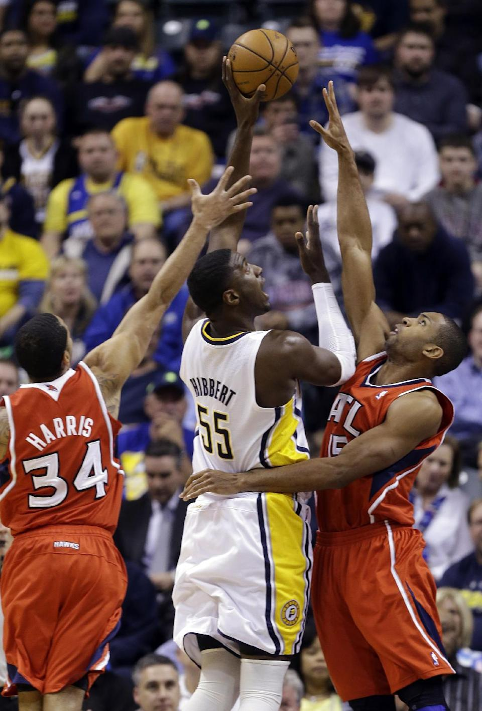 Indiana Pacers center Roy Hibbert (55) shoots between Atlanta Hawks guard Devin Harris, left, and center Al Horford in the first half of Game 2 of a first-round NBA basketball playoff series in Indianapolis, Wednesday, April 24, 2013. (AP Photo/Michael Conroy)