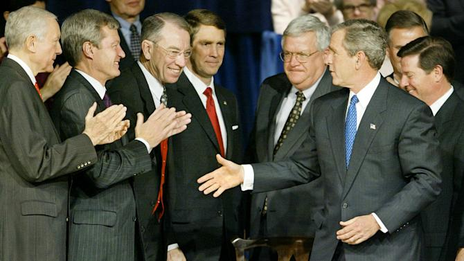 FILE - In this Dec. 8, 2003, file photo President George W. Bush greets applauding Congressional leaders as he signs into law the Medicare prescription drug benefit at the Daughters of the American Revolution's Constitution Hall in Washington. Deficit hawks note the inconsistency of 2012 Republican presidential candidates who say they'll try to repeal President Barack Obama's health overhaul, but nod to another massive health care entitlement with unfunded future costs of over $7 trillion created by Republicans. From left to right: Sen. Orrin Hatch, R-Utah, Sen. Max Baucus, D-Mont., Sen. Charles Grassley, R-Iowa, Senate Majority Leader Sen. Bill Frist, R-Tenn., Speaker of the House of Representatives Dennis Hastert, R-Ill., President Bush, and Sen. John Breaux, D-La., partially obscured, and House Majority Leader Tom DeLay, R-Texas.  (AP Photo/J. Scott Applewhite, File)