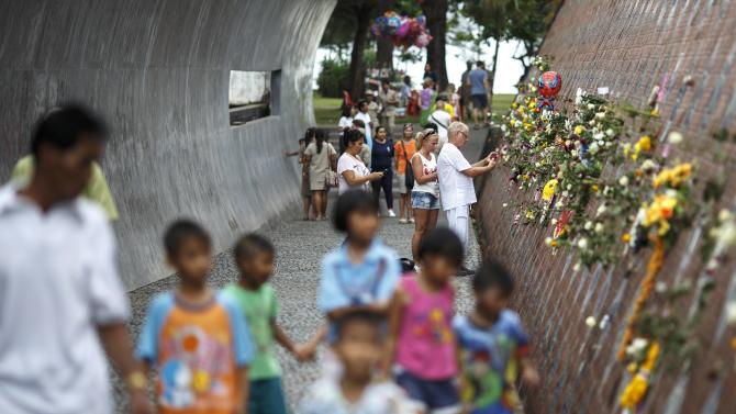 People pay their respects to the victims of the 2004 tsunami at a wave shaped memorial in Ban Nam Khem