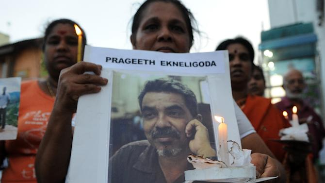 Sandhya Eknaligoda (R), wife of missing Sri Lankan cartoonist and journalist Prageeth Eknaligoda, holds up a placard bearing his image during a protest rally in Colombo on January 24, 2012