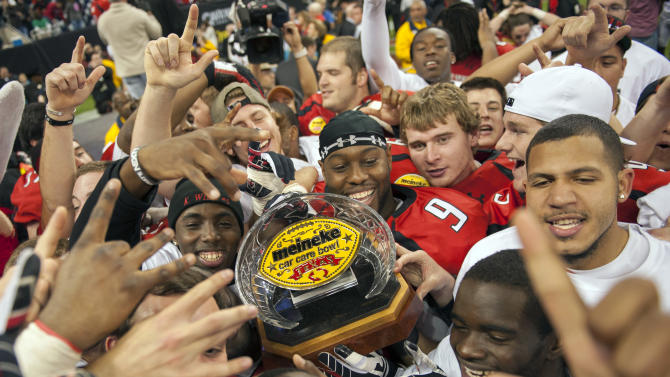Texas Tech players celebrate with the championship trophy after winning the Meineke Car Care Bowl NCAA college football game against Minnesota, Friday, Dec. 28, 2012, in Houston. Texas Tech defeated Minnesota 34-31. (AP Photo/Dave Einsel)