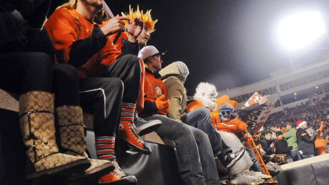 Oklahoma State fans sit on the edge of the stadium wall in the remaining minutes of the fourth quarter of an NCAA college football game against Oklahoma in Stillwater, Okla., Saturday, Dec. 3, 2011. Fans jumped from the wall to celebrate on the field following Oklahoma State's defeat of rival Oklahoma 44-10. (AP Photo/Brody Schmidt)