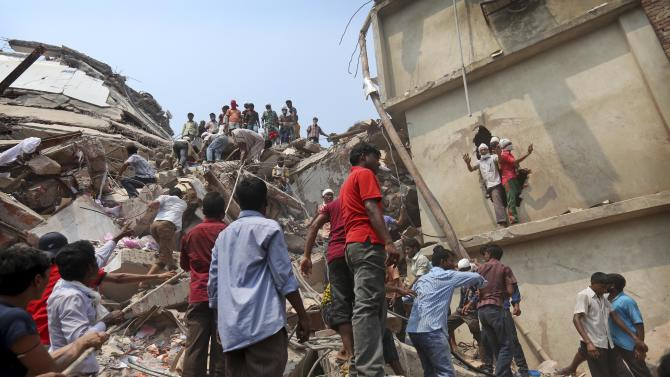 Bangladeshi rescue workers work at the site of a building that collapsed Wednesday in Savar, near Dhaka, Bangladesh, Friday, April 26, 2013. The death toll reached hundreds of people as rescuers continued to search for injured and missing, after a huge section of an eight-story building that housed several garment factories splintered into a pile of concrete.(AP Photo/Kevin Frayer)