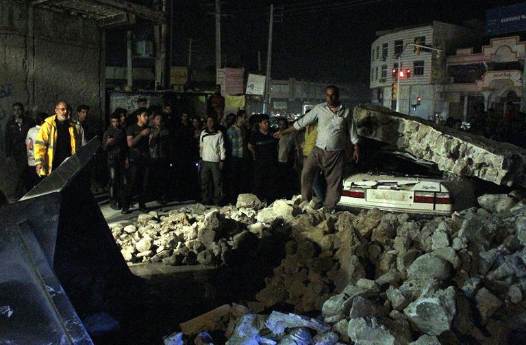 A picture obtained from Iran's ISNA news agency shows Iranians gathering amid rubble in the western city of Borazjan, on November 28, 2013, after a 5.7 magnitude earthquake struck the country
