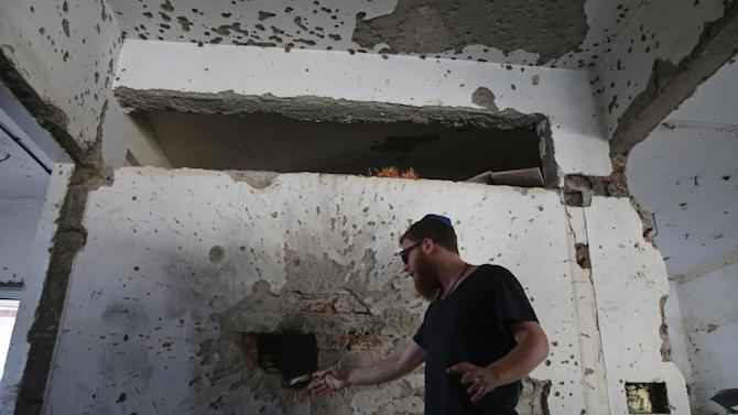 Naftali Charter, Chief of Security at Chabad Center, points to a wall riddled with bullet marks from the 2008 terror attack, during a tour with the media of the site of the attack, on the 6th anniversary of the attack in Mumbai, India, Wednesday, Nov 26, 2014. The attack by Pakistani gunmen in India's financial capital on Nov. 26, 2008 killed 166 people and shattered relations between the nuclear-armed neighbors. (AP Photo/Rafiq Maqbool)