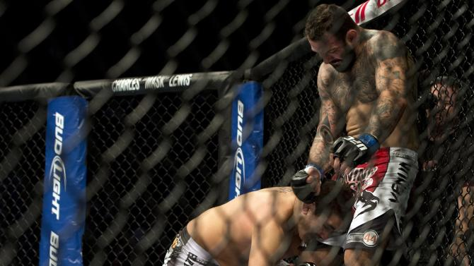 Patrick Cote, left, from Canada, is knocked down by Alessio Sakara during their UFC 154 middleweight bout on Saturday, Nov. 17, 2012, in Montreal. Cote won the bout after Sakara was disqualified. (AP Photo/The Canadian Press, Ryan Remiorz)