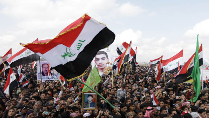 Iraqis chant anti-government slogans as they wave national flags and hold posters of slain protesters in Fallujah, 40 miles (65 kilometers) west of Baghdad, Iraq, Friday, Feb. 1, 2013. Last week, five protesters and two Iraqi soldiers were killed in clashes in Fallujah. Tens of thousands of Sunni protesters blocked a major highway in western Iraq on Friday, as an al-Qaida-affiliated group called on Sunnis to take up arms against the Shiite-led government. (AP Photo/ Khalid Mohammed)