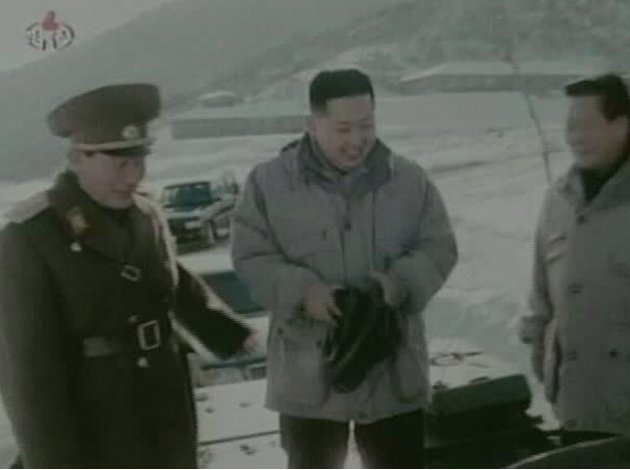 """In this undated image made from KRT video, North Korea's new young leader Kim Jong Un, center, smiles as he stands on a military vehicle at an undisclosed place in North Korea, aired Sunday, Jan. 8, 2012. Kim Jong Un, who was named """"supreme leader"""" of North Korea's people, ruling Workers' Party and military following the death last month of his father, Kim Jong Il, was shown observing firing exercises and posing for photographs with soldiers in footage that was shot before his father's death and aired as a documentary Sunday."""