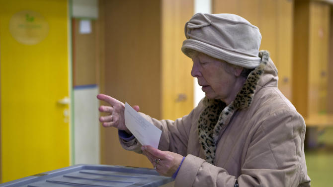 A voter casts her ballot at the polling station in Ljubljana, Slovenia, Sunday, Dec. 2, 2012. Small, crisis-hit EU member Slovenia is choosing a president in an atmosphere of uncertainty and growing discontent with cost-cutting measures designed to avoid an international bailout. (AP Photo/Darko Bandic)