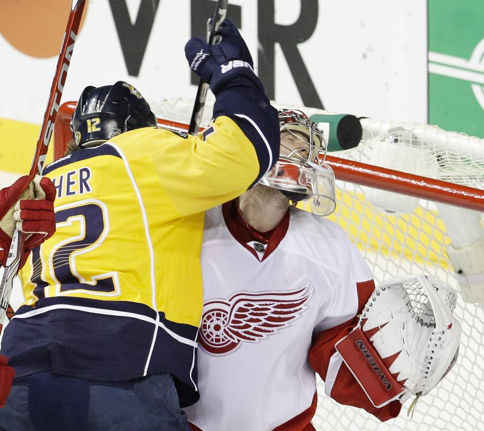 Nashville Predators center Mike Fisher (12) collides with Detroit Red Wings goalie Jimmy Howard, right, in the first period of Game 5 of a first-round NHL hockey playoff series on Friday, April 20, 2012, in Nashville, Tenn. (AP Photo/Mark Humphrey)