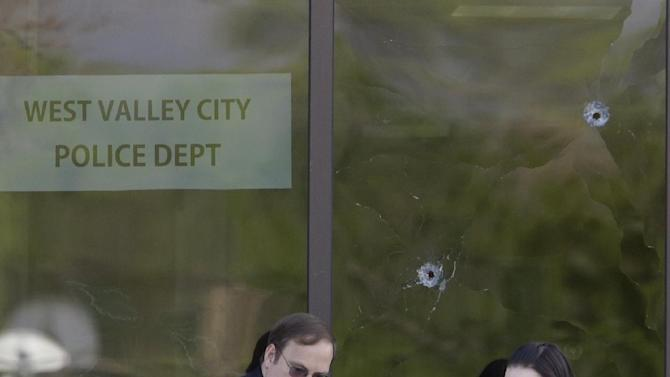 Members of the West Valley City Police Forensics Unit examine bullets holes in a window at the West Valley City Police Department Monday, April 29, 2013, in West Valley City, Utah. Authorities in a Salt Lake City suburb say a man shot after pulling a gun in a police lobby told officers months ago that he wanted to be shot by police. West Valley City police Sgt. Jason Hauer says the man shot Monday morning was 39-year-old James Ramsey Kammeyer. Hauer says Kammeyer entered the lobby around 8:30 a.m. Monday and asked an officer to come out from behind a partition. When several officers came to help, Kammeyer pulled out a gun and at least one of the officers shot him multiple times. (AP Photo/Rick Bowmer)