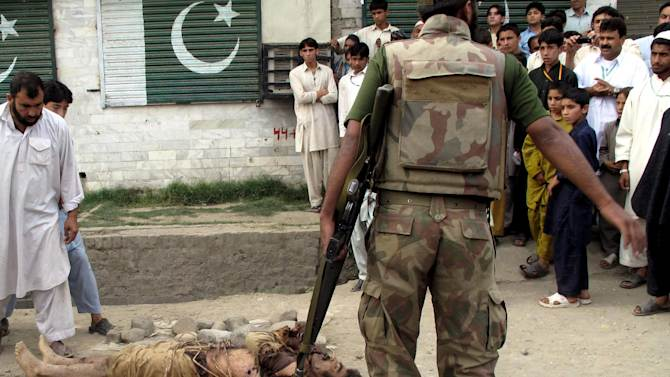 FILE-  In this April 26, 2010, file photo, Pakistani residents of Kanju in Pakistan's troubled Swat valley look at a dead body of an alleged militant, killed by security forces. Pakistan has spent nearly five years under civilian rule, an unusually long stretch for a 65-year-old country prone to military coups. But as the firing squad footage and several other prominent scandals suggest, the army remains largely unwilling to hold itself accountable to the public. This despite some pressure from more active media and judiciary and despite hopes that the military would rethink its ways after the humiliation it suffered following the unilateral U.S. raid that killed Osama bin Laden. (AP Photo/Sherin Zada, File)