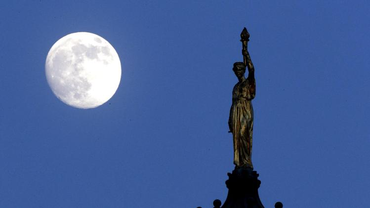 "The moon in its waxing gibbous stage is shines behind a statue entitled ""Enlightenment Giving Power"" by John Gelert, which sits at the top of the dome of the Bergen County Courthouse in Hackensack, N.J., Friday, June 21, 2013. The moon, which will reach its full stage on Sunday, is expected to be 13.5 percent closer to earth during a phenomenon known as supermoon. (AP Photo/Julio Cortez)"