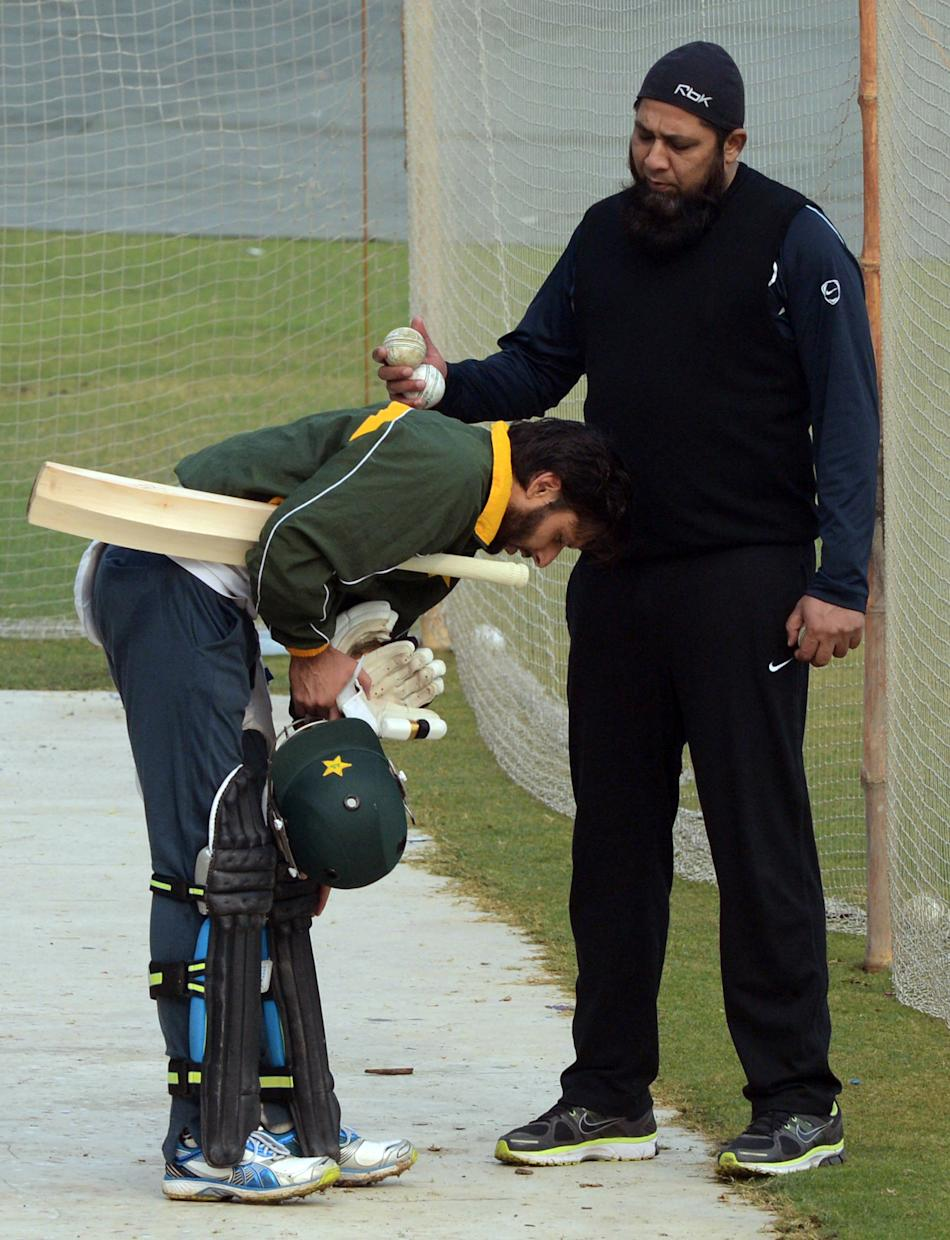 Former Pakistani cricket captain and team batting coach Inzamam-ul Haq (R) and cricketer Shahid Afridi (L) interact during a team practice session at the Gaddafi stadium in Lahore on December 15, 2012
