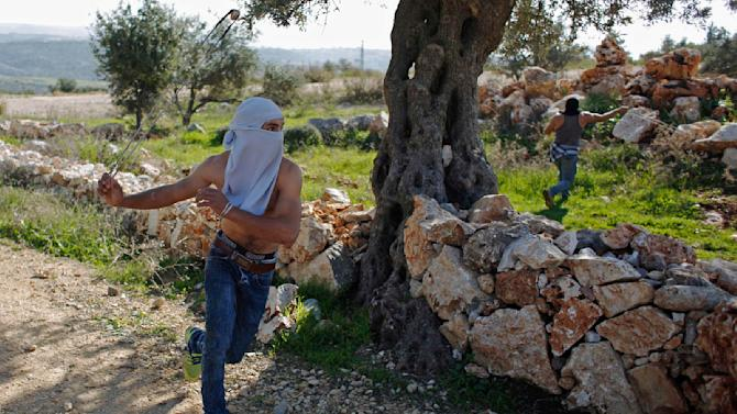 A Palestinian protester uses a slingshot to throw stones at Israeli troops during clashes following a demonstration against Jewish settlements in the West Bank village of Bilin