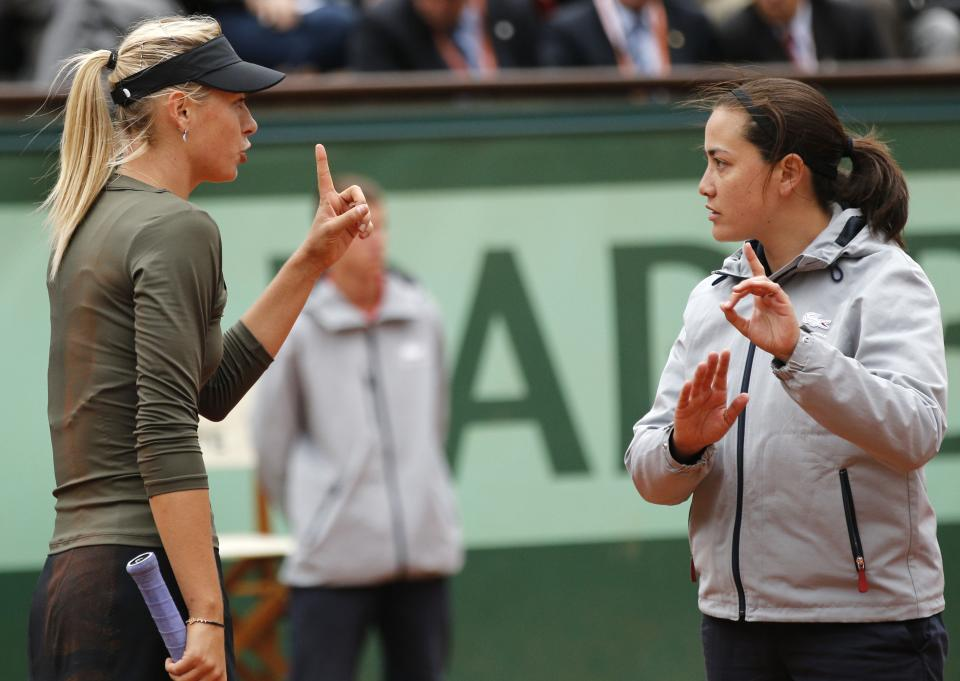 Russia's Maria Sharapova, left, argues with umpire Julie Minori Kjendlie, of Norway, as she plays Czech Republic's Klara Zakopalova during their fourth round match in the French Open tennis tournament at the Roland Garros stadium in Paris, Monday, June 4, 2012.  (AP Photo/Christophe Ena)