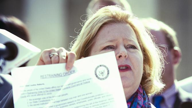 Janet Porter pf Faith2Action, displays a Restraining Order while speaking at a Restrain the Judges news conference in front of the Supreme Court in Washington, Monday, April 27, 2015. The opponents of same-sex marriage are urging the court to resist embracing what they see as a radical change in society's view of what constitutes marriage. (AP Photo/Cliff Owen)