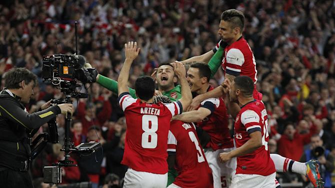 Arsenal players celebrate their win against Wigan Athletic at the end of their English FA Cup semifinal soccer match at Wembley Stadium in London, Saturday, April 12, 2014