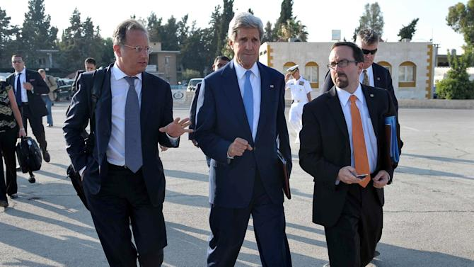 U.S. Secretary of State John Kerry, center, makes his way to board a flight to reach the West Bank city of Ramallah, where he is expected to hold new talks with Palestinian president Mahmuod Abbas on Friday, July 19, 2013 in the Jordanian capital Amman. Kerry Friday met earlier with chief Palestinian negotiator Saeb Erakat in a final push to get a peace bid back on track before heading home. U.S. Secretary of State John Kerry stepped up his drive Friday to get Israelis and Palestinians back to the negotiating table, facing Palestinian reluctance over his formula for resuming peace talks after nearly five years.(AP Photo/Mandel Ngan, Pool)
