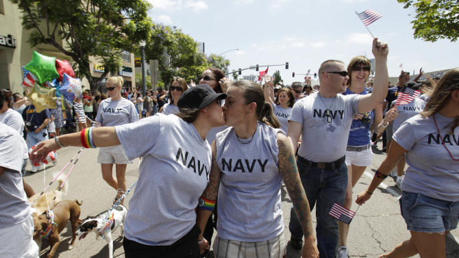 """FILE - In this July 16, 2011 photo, two women, both active duty sailors in the Navy who gave their names as Nikki, left, and Lisa, kiss as they march in the Gay Pride Parade in San Diego. Defense Secretary Leon Panetta is thanking gay military members for their service, as the Pentagon prepares to mark June as gay pride month with an official salute.  In a video message to the troops Friday, June 15, 2012, Panetta says that with the repeal last year of the """"Don't Ask, Don't Tell"""" law that prohibited gays from serving openly in the military, gays and lesbians can now be proud to be in uniform. (AP Photo/Gregory Bull)"""