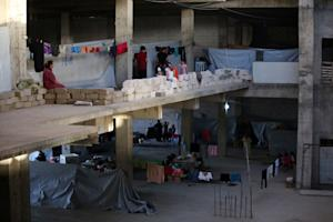 Iraqi Christians take shelter inside a building under …