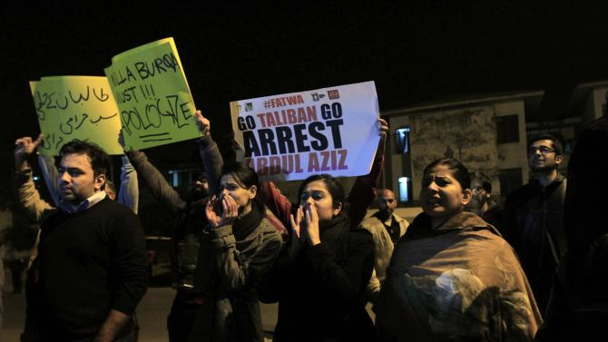 People hold signs and chant slogans during a protest outside a police station in Islamabad