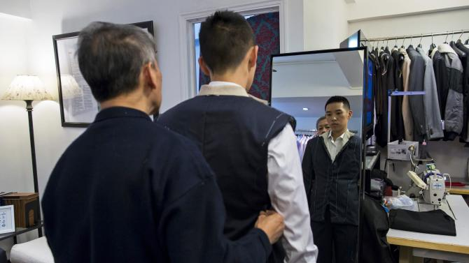 Tailor Cheung Wan-sun checks a customer's new outfit before the final touches, inside a bespoke tailoring firm in Hong Kong