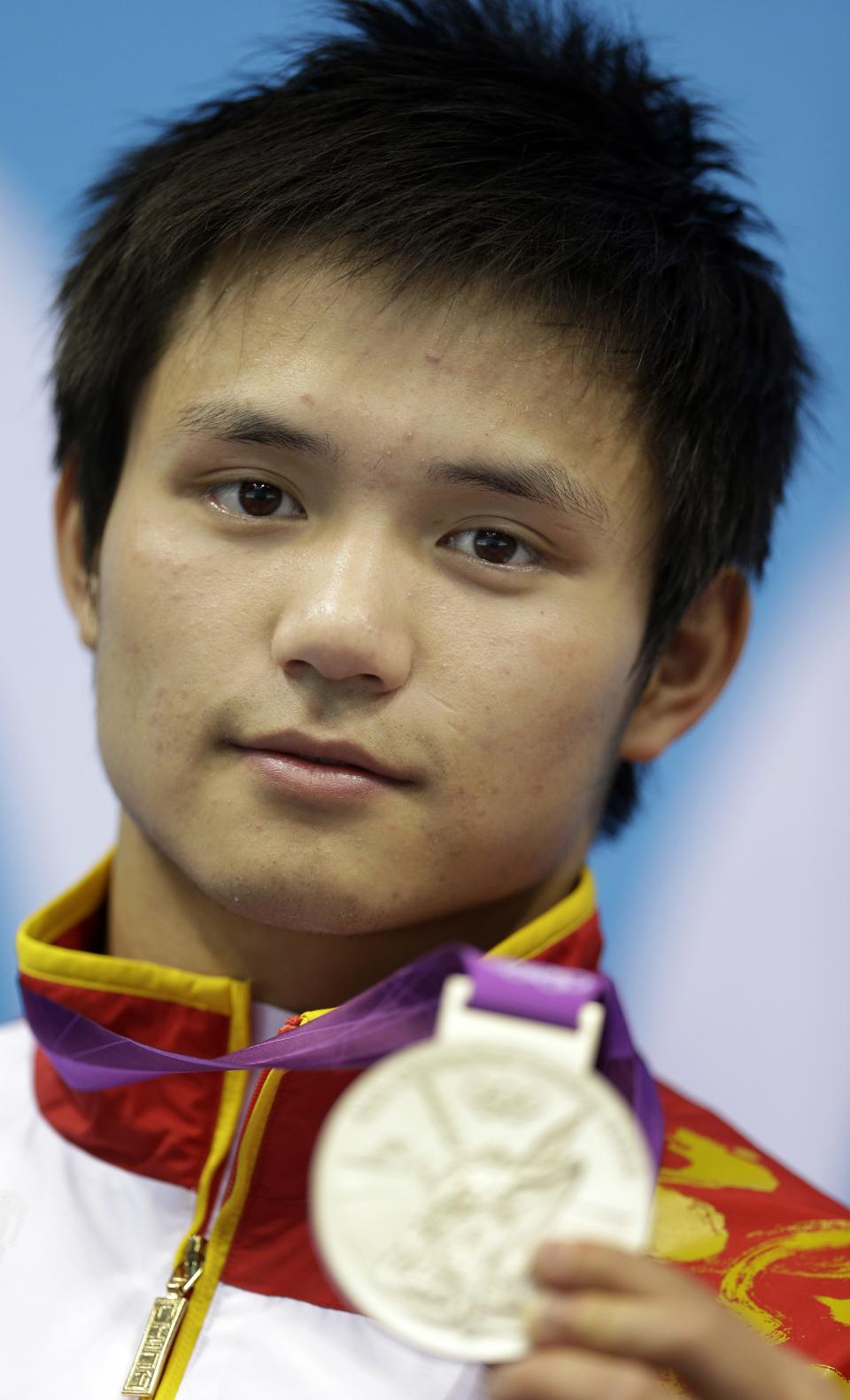 Silver medalist Qiu Bo from China poses during the medal ceremony for the men's 10-meter platform diving final at the Aquatics Centre in the Olympic Park during the 2012 Summer Olympics in London, Saturday, Aug. 11, 2012. (AP Photo/Michael Sohn)